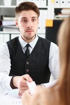 スーツの男性の手が訪問者に空白のテレホンカードを与える