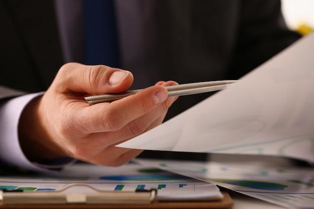Мужская рука в костюме держит серебряную ручку в офисе