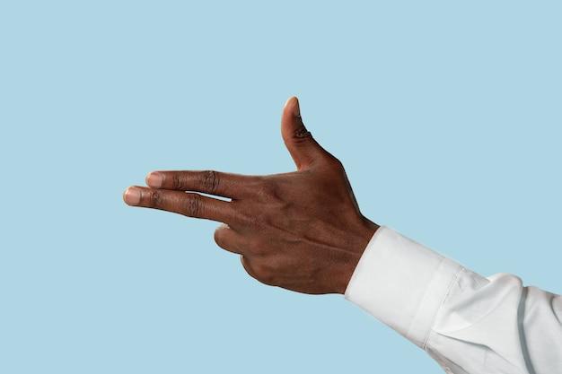 青い背景に分離された銃、拳銃またはピストルのジェスチャーを示す白いシャツの男性の手。
