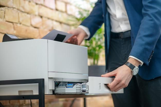 Мужская рука в наручных часах открывает контейнер в гаджете и перебирает листы бумаги в офисе