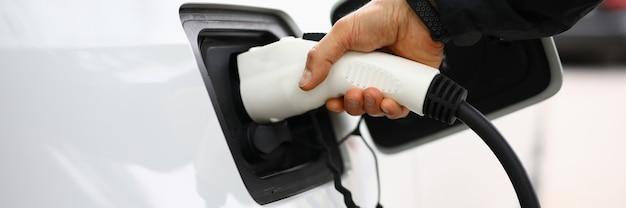 남성 손은 전기 흰색 총을 자동차에 삽입합니다. 흰색 전기 자동차는 충전소에서 충전됩니다.