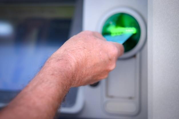 돈을 인출하기 위해 은행 기계에 신용 카드를 삽입하는 남성 손