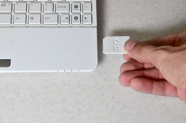 A male hand inserts a white compact sd card into the corresponding