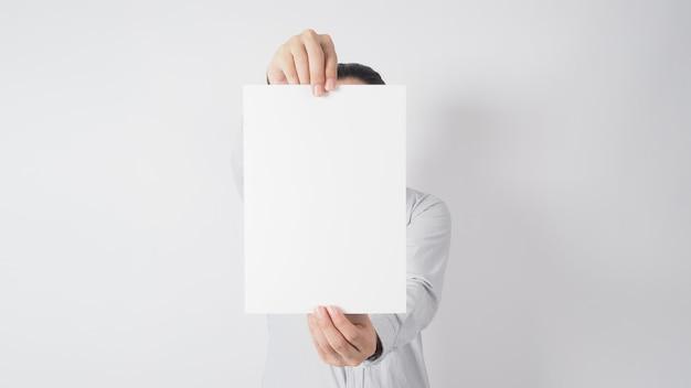 男性の手は白紙を持っており、白い背景に長袖シャツを着ています。
