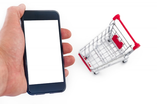 Male hand is holding a phone. metal cart on a white.