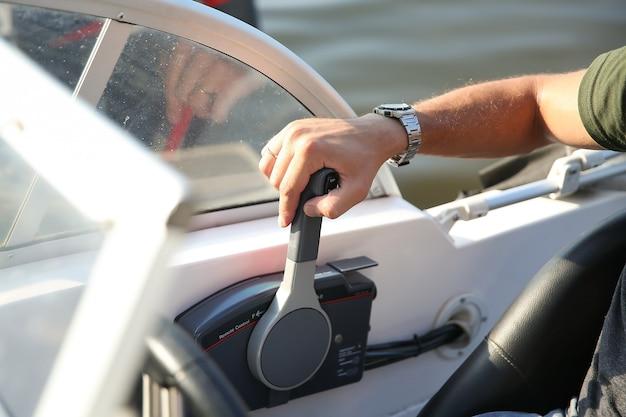 男性の手は白いモーターボートのコントロールレバーにクローズアップ