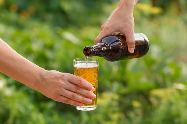 남자 손이 여자가 들고 있는 유리잔에 맥주를 붓고 있다