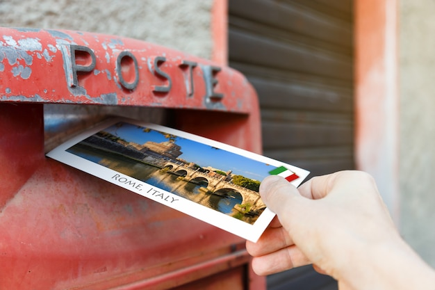 Male hand is putting a postcard in a red postbox in rome, italy, europe