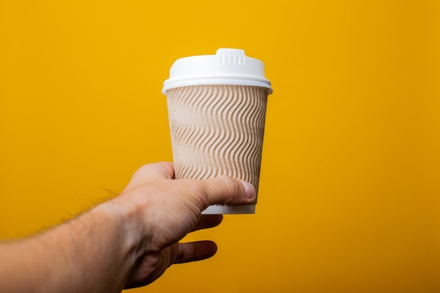 Male hand is serving a cardboard glass on a yellow background.