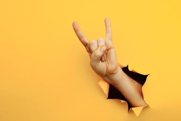 黄色の背景にロックンロールジェスチャーパーティーヤギを作る男性の手