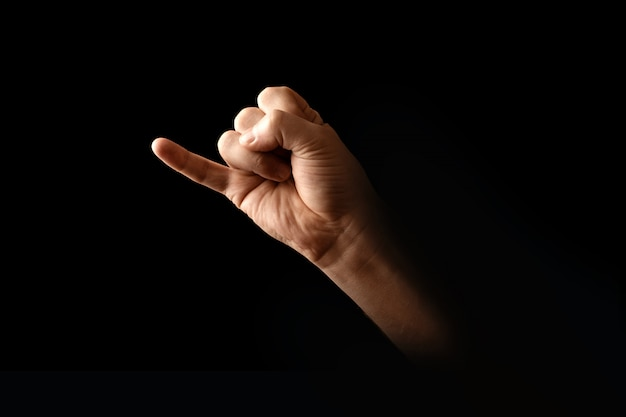 Male hand making pinky swear sign over dark background