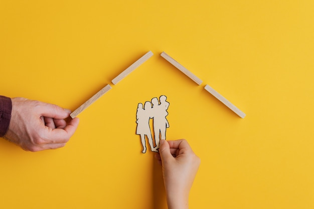 Male hand making a roof of wooden pegs for a child to place paper cut family silhouette under it.  conceptual image of safety and security. over yellow background.