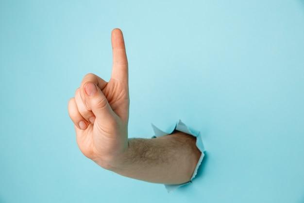 青い紙の穴からサインを作る男性の手
