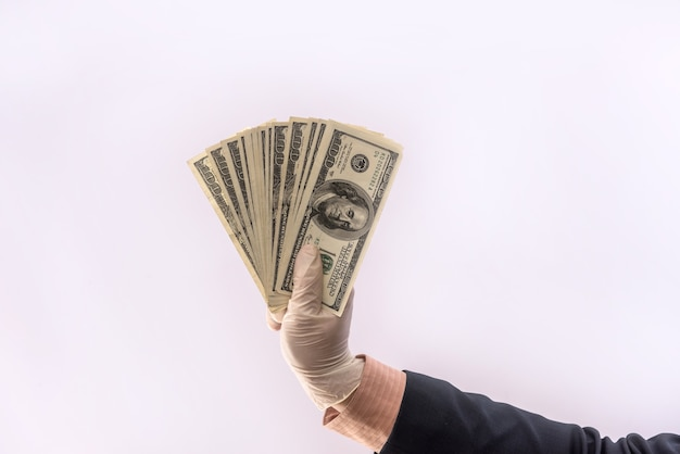 Male hand in medical glove holds us money bills for protection against covid-19 (coronavirus) isolated.