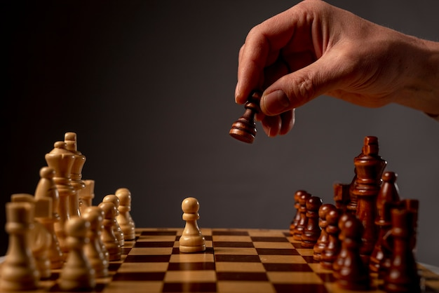Male hand moving pawn on chess board, starting game. making business decision concept.