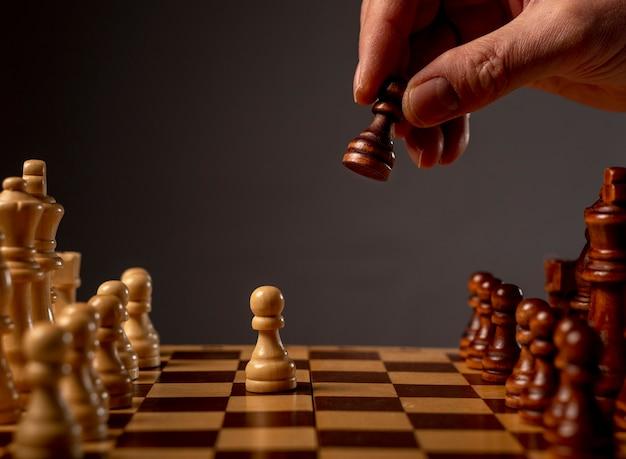 チェス盤でポーンを動かす男性の手、ゲームを開始します。ビジネスの意思決定の概念を作成します。
