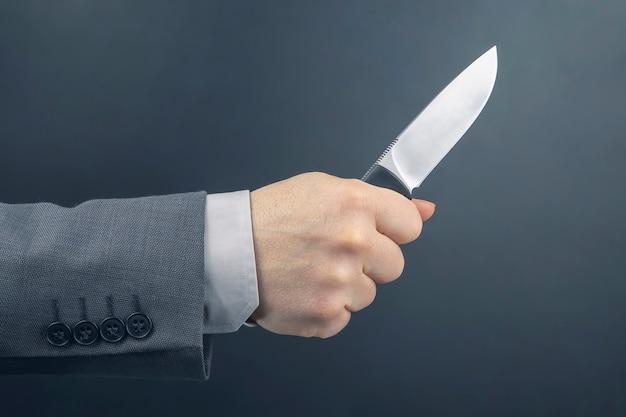 비즈니스 남자의 남성 손에 칼을 보유하고있다. 위협 및 범죄 행위. 필수 생활 도구