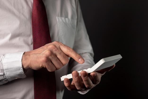 Мужская рука бизнесмена, держащего калькулятор