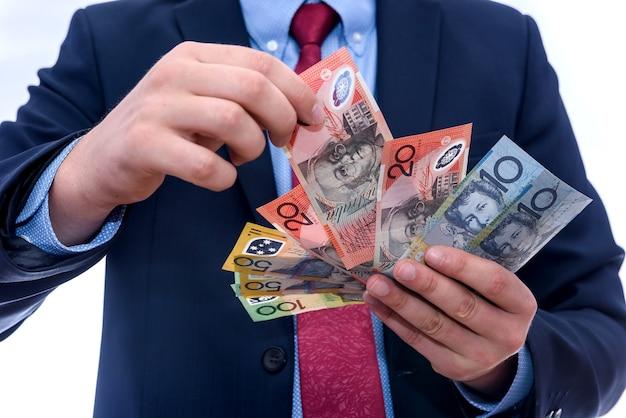 白で隔離されるオーストラリアドル紙幣を提供する男性の手