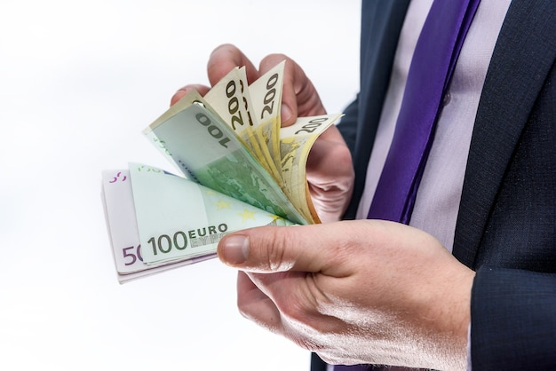 Male hand offering euro banknotes close up