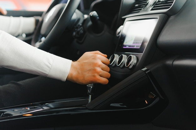 車のトランスミッションのシフトレバーに男性の手