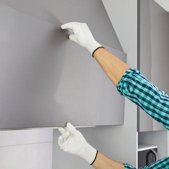 Мужской ручной открытый кухонный шкаф без ручки. закройте вверх.
