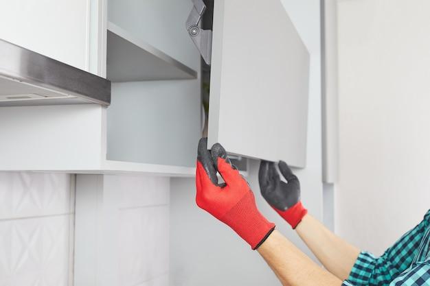 男性の手はハンドルなしのキッチン食器棚を開きます。