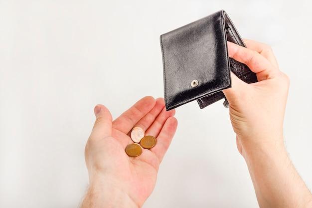 Мужская рука раскрывая бумажник и подсчитывает монетки на белой предпосылке. мировой экономический кризис. финансовая проблема безработных, концепция банкротства.