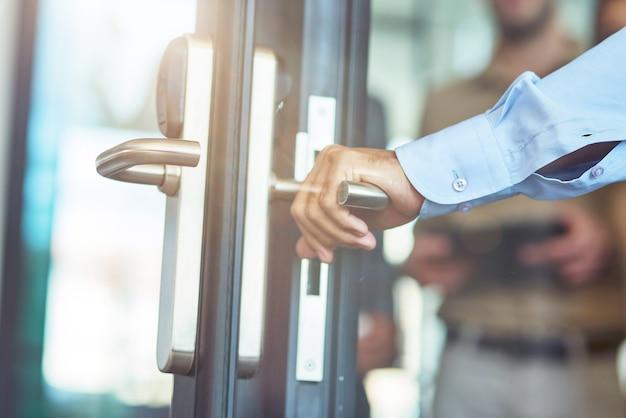 現代のオフィスでガラスのドアを開く男性の手クローズアップショット