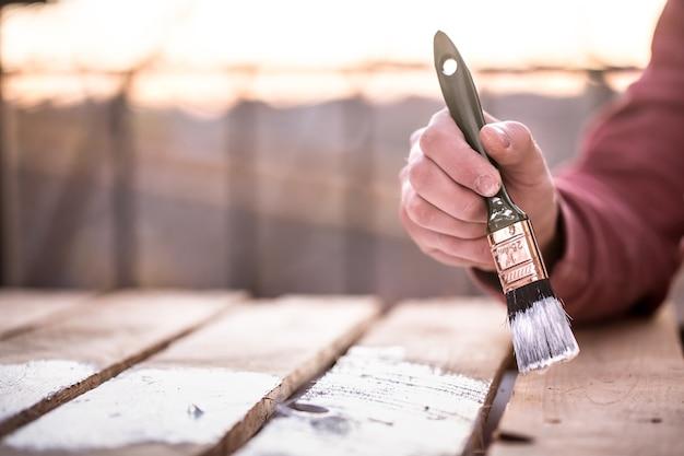 男性の手が木材、絵画の概念、クローズアップ、テキストのための場所に白いペンキで塗料します。