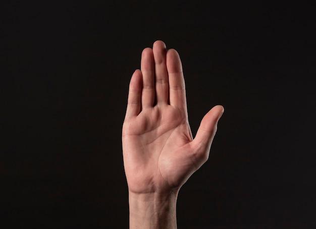 男性の手のひらのジェスチャーは、黒い背景の上に停止します。