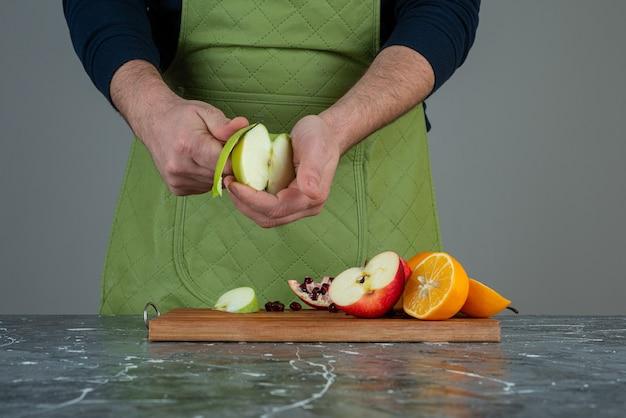 テーブルの上の木の板の上に新鮮なリンゴをはがしている男性の手。