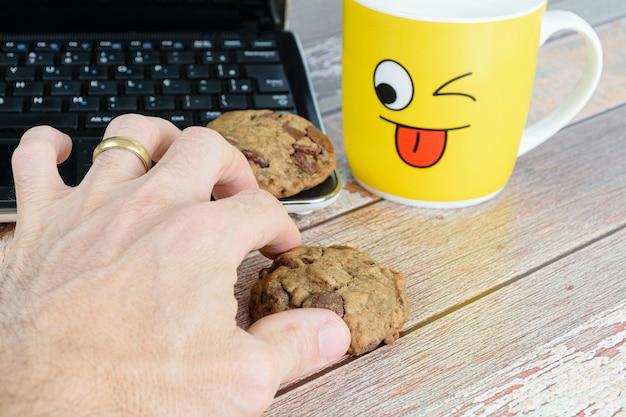 チョコレートの滴でクッキーを拾う男性の手。ミルクとラップトップと黄色のマグカップ。 eラーニングのために一時停止します。