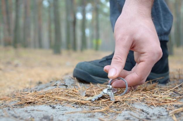 Мужская рука подбирая потерянные ключи от земли в пути древесины ели осени. концепция поиска ценной вещи и удачи