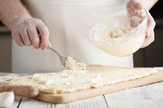 Мужская рука собирает расплавленный сыр из стеклянной чаши для пирога с сыром