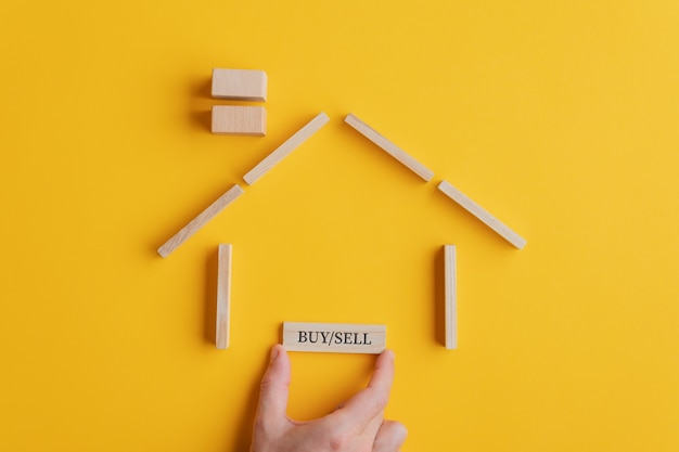 부동산 시장의 개념적 이미지에 나무 블록과 못으로 만든 집에 매수 / 매도 기호를 배치하는 남성 손. 노란색 배경 위에.