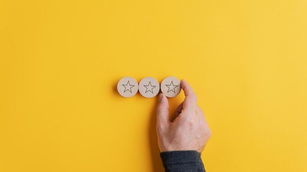 黄色の背景の上に一列に星の形をした3つの木製のカット円を置く男性の手。