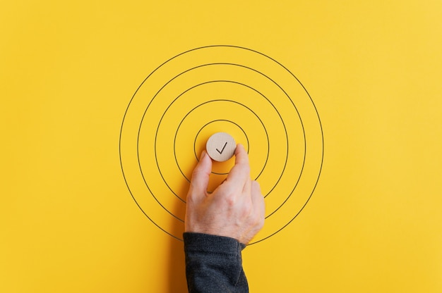 Male hand placing a wooden cut circle with check mark on it in the middle of drawn circles over yellow background.