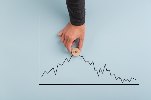 Male hand placing a wooden cut circle with date sign on it on top of a statistical graph
