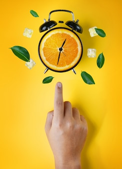 Male hand pointing alarm clock of orange fruit green leaves and ice cube flying around