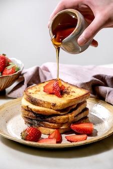 Мужская рука наливает кленовый сироп из керамического кувшина на стопку французских тостов со свежей клубникой на тарелке и розовой тканевой салфеткой над белым столом