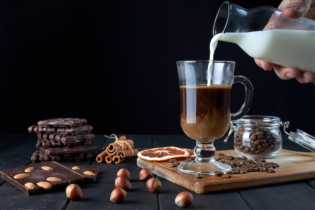 Male hand pouring milk into glass of black coffee with chocolate, cinnamon sticks and slices of dried grapefruit on black background side view.