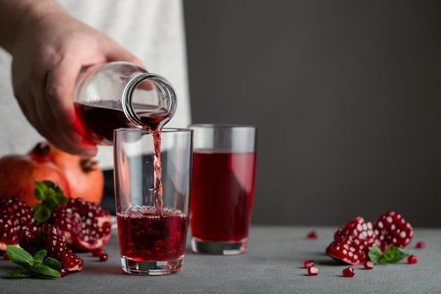 ボトルからグラスにザクロジュースを注ぐ男性の手。近くにはいくつかのザクロがあります。