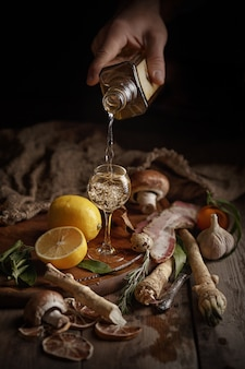 Male hand pours alcohol into a glass.. composition of various foodstuffs on a wooden table. top view.