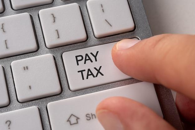 男性の手がキーボードのボタンのpay taxを押します。