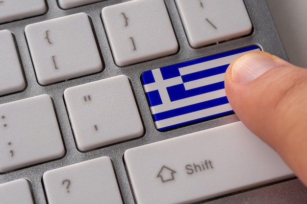 Мужская рука, нажав кнопку клавиатуры с флагом греции на нем.