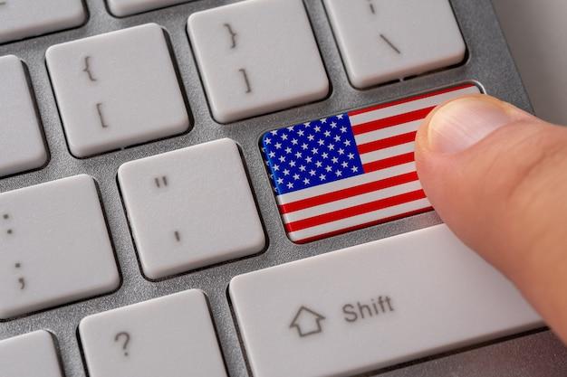 Мужская рука, нажав кнопку клавиатуры с флагом сша на нем.