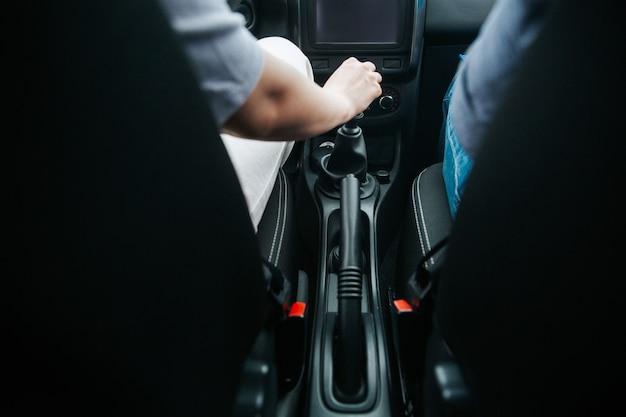 새 차에 자동 기어 시프터를 당기는 남성 손. 수동 기어 박스. 자동차 컨셉을 운전하는 즐거움. 흐리게 전면 전경과 남자의 손에 초점.