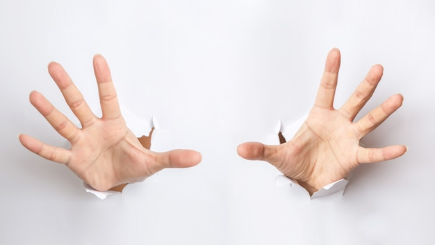 Male hand  punching through the paper