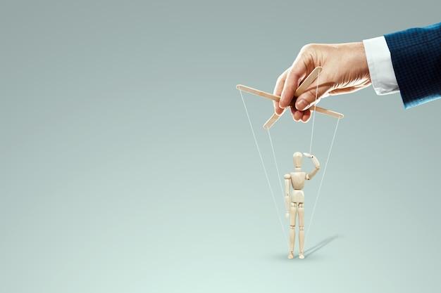 남성 손, 인형 조종사는 꼭두각시, 인형 경례, 군인을 제어합니다. 군대, 명령, 조작, 통제, 군대의 개념.